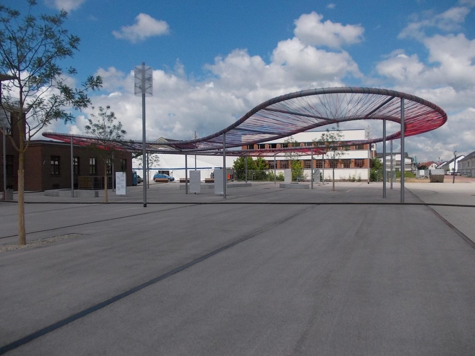 Stahlbau Kunstwerk Kelsterbach mit gebogenen Großrohren bespannt mit bunten Seilen